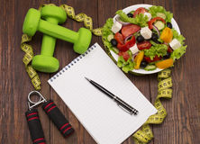 Dumbbell, vegetable salad and measuring tape on rustic wooden table. Stock Images
