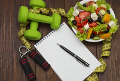 Dumbbell, vegetable salad and measuring tape on rustic wooden table. Stock Photography