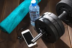Dumbbell, water bottle, blue towel, telephone, headphones on the wooden floor of the gym stock photos