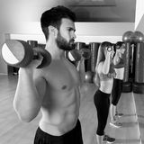 Dumbbell weightlifting man women group at mirror Stock Image