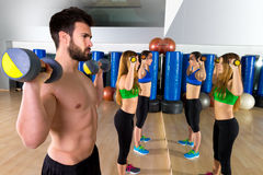 Dumbbell weightlifting man women group at mirror Stock Photography