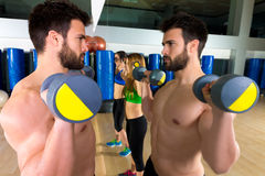 Dumbbell weightlifting man women group at mirror Royalty Free Stock Photography