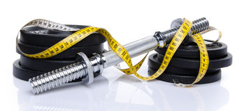 Dumbbell with weights and tape measure Royalty Free Stock Photo