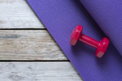 Dumbbell and yoga mat on table royalty free stock images