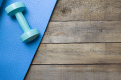 Dumbbell and yoga mat. On wood table Royalty Free Stock Image