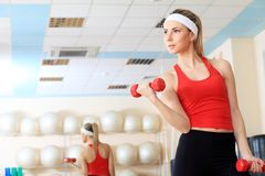 Dumbbells. Young sporty woman in the gym centre Royalty Free Stock Images