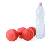 Dumbbells. Isolated red dumbbells with a bottle of mineral water Royalty Free Stock Images