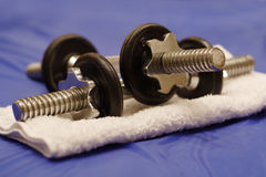 Dumbbells. A pair of dumbbells and a towel, on a blue gym mat royalty free stock photo