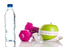 Dumbbells, Apfel, Maßband und bootle des Wassers Lizenzfreie Stockfotos