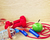 Dumbbells, apple, bottle of water and jump rope Stock Image