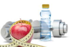 Dumbbells with an apple and measuring type Stock Photography
