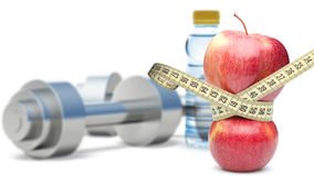 Dumbbells with an apple and measuring type Stock Photos