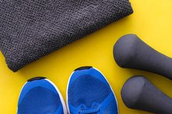 Sport flatlay background. Dumbbells, blue sneakers and gray towel. Sport fitness accessories stock photo
