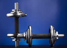 Dumbbells on blue Stock Images