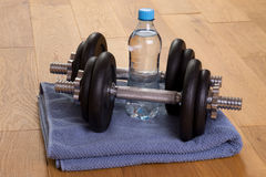 Dumbbells and bottle of water in a gym Royalty Free Stock Images