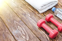 Dumbbells and a bottle of water with towel on wooden background, concept preparing to fitness sports equipment top view. Royalty Free Stock Photography