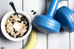 Dumbbells and bowl with yogurt Royalty Free Stock Photos