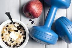 Dumbbells and bowl with yogurt Stock Photo