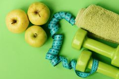 Dumbbells in bright green color, twisted measure tape, towel, fruit royalty free stock photography