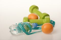 Dumbbells in bright green color, water bottle, measure tape, fruit. Dumbbells in bright green color, water bottle, measure tape and fruit on white background stock images
