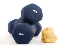 Dumbbells and candle Royalty Free Stock Photography