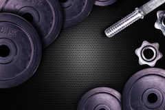 Dumbbells on carbon background. Dumbbells and weights are lying on the floor in the gym. Barbell set and gym equipment. Metal stock photography