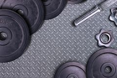 Dumbbells on carbon background. Dumbbells and weights are lying on the floor in the gym. Barbell set and gym equipment. Metal stock images