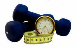 Dumbbells, clock and measuring tape Stock Images
