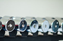 Dumbbells of different scales lie on the sports Royalty Free Stock Photos