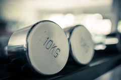 Dumbbells of different scales lie on the sports shelf Royalty Free Stock Photography