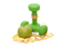 Dumbbells for fitness, green apple and centimeter measuring tape. On a white background Stock Image
