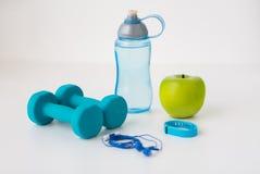 Dumbbells, fitness tracker, earphones and bottle Royalty Free Stock Photo