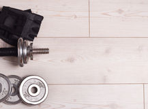 Dumbbells and gloves on the floor Stock Images