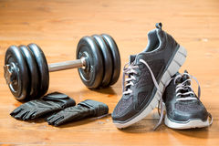Dumbbells, gloves and sneakers in black on a dark wooden floor Stock Image