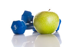 Dumbbells and a green apple Royalty Free Stock Photos
