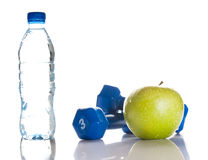 Dumbbells, green apple and a bottle of fresh water Stock Photo