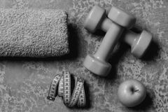 Dumbbells in green color, apple, towel and cyan measuring tape on grey texture background. Sports and healthy training. Idea. Workout and healthy lifestyle stock photography