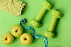 Dumbbells in green color, twisted measure tape, towel and fruit royalty free stock image