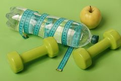 Dumbbells in green color, water bottle, measure tape and fruit. On green background. Healthy lifestyle and food concept. Healthy regime equipment. Bottle tied stock image