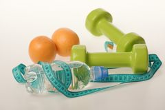 Dumbbells in green color, water bottle, measure tape and fruit. On white background. Sports and healthy regime equipment. Barbells made of plastic near juicy stock image