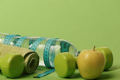 Dumbbells in green color, water bottle, measure tape, towel, fruit. Dumbbells in green color, water bottle, measure tape, towel and fruit on green background stock photos