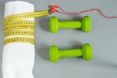 Dumbbells green, red headphones white towel, measuring tape. Top view, Fitness and diet concept background. Stock Photo