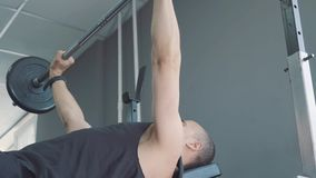 Dumbbells in the gym - muscle training. The man lifts dumbbells in the gym. The rolled big man trains with dumbbells stock video