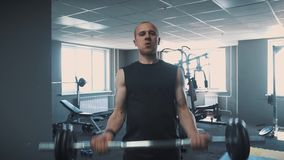 Dumbbells in the gym - muscle training. The man lifts dumbbells in the gym. The rolled big man trains with dumbbells stock video footage