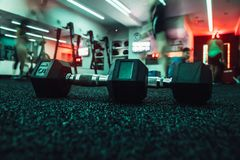 Dumbbells in gym with people doing sport workout. Dumbbells in gym with people doing sport workout stock photos