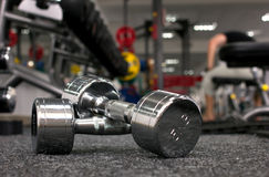 Dumbbells in gymnasium. Two dumbbells in gymnasium on blurred background stock photo