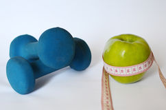 Dumbbells i pomiarowa taśma wokoło jabłka Fotografia Royalty Free