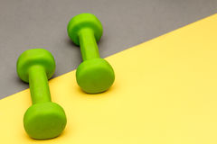 Dumbbells isolated on grey and yellow background. Stock Images