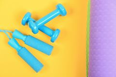Dumbbells and jump rope in cyan blue color. On yellow and purple background, top view. Barbells and skipping rope on yoga mat. Sports and healthy lifestyle royalty free stock image