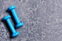Dumbbells made of cyan blue plastic on grey texture background. Sports and healthy lifestyle concept. Pair of barbells in small size, copy space. Shaping and royalty free stock photography
